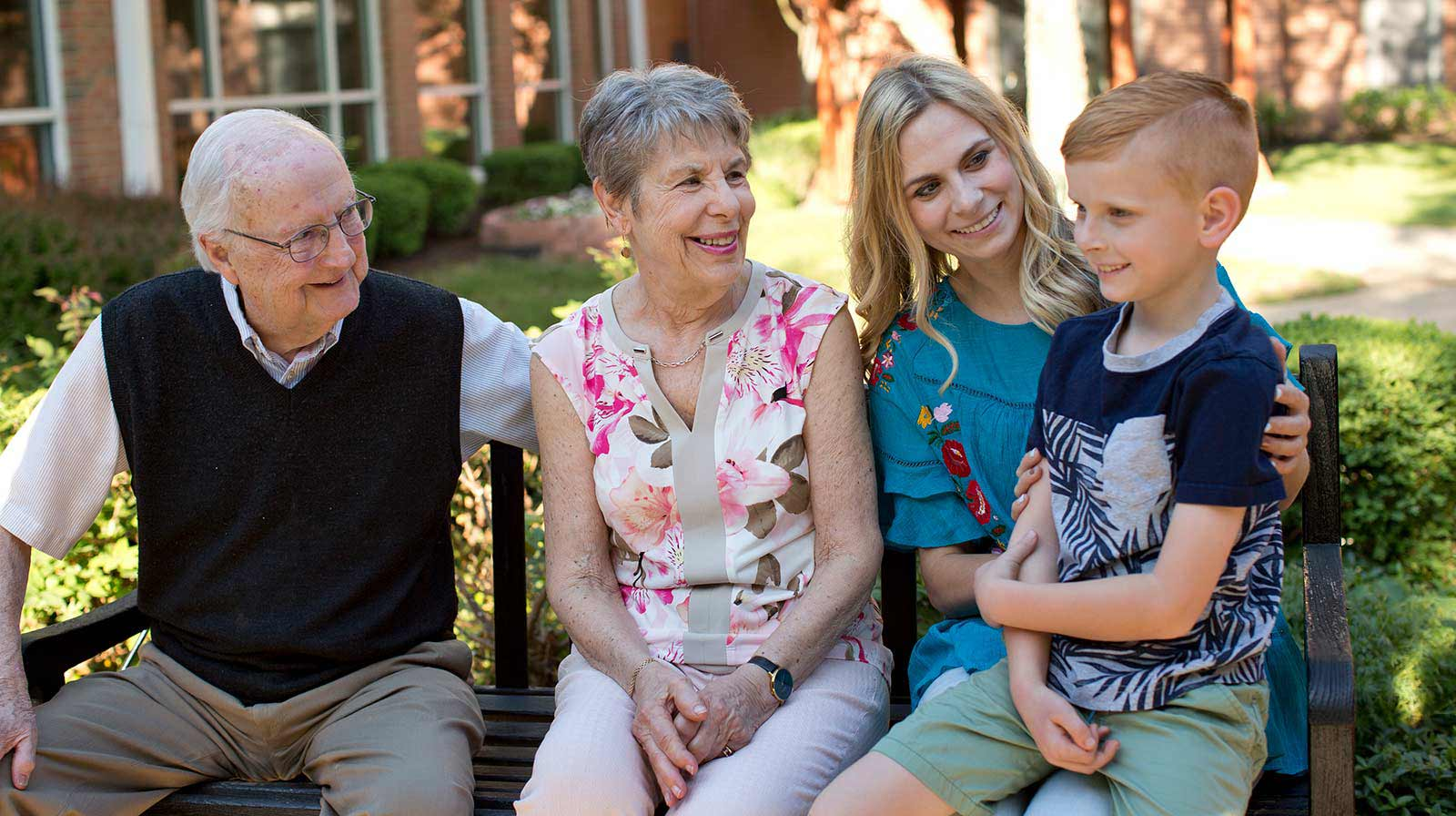 A family sitting on a park bench at Kingswood Senior Living Located in Kansas City, MO.