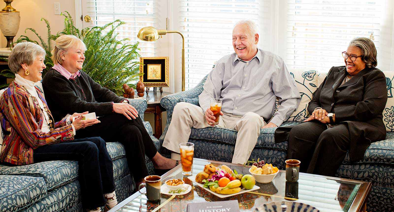 Two couples sitting on sofa at Kingswood Senior Living Located in Kansas City, MO.