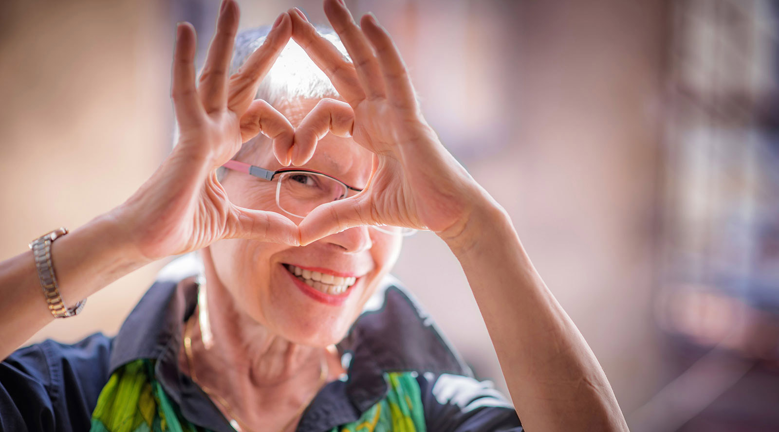 A women making a heart symbol with her hands.