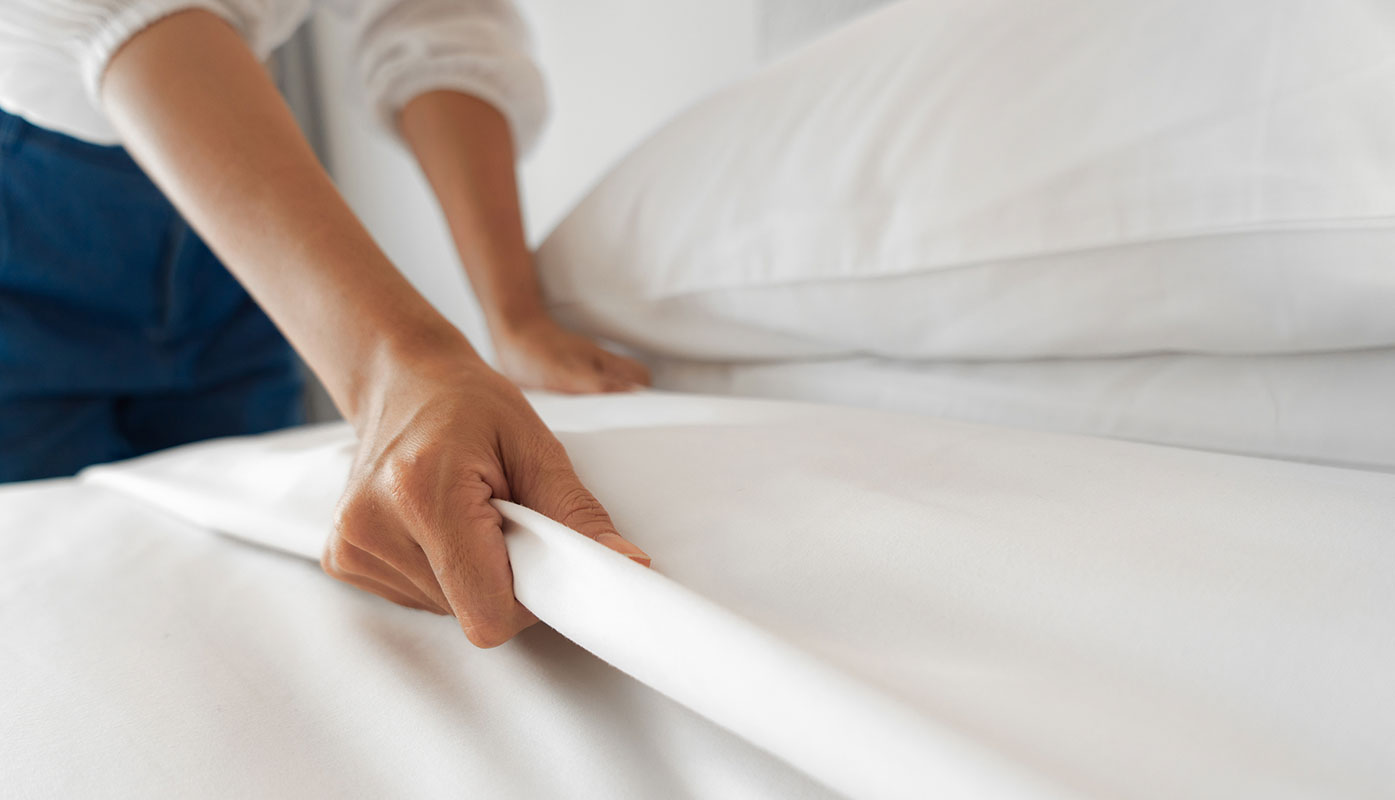 White sheets on a bed.