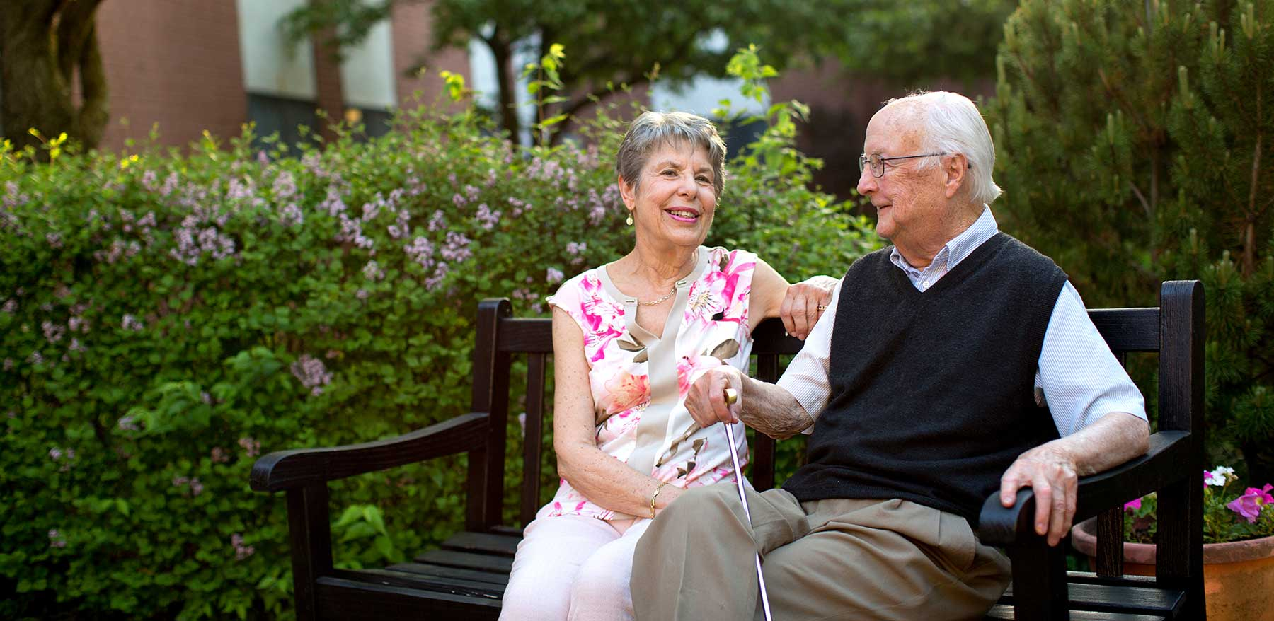 A couple sitting on a park bench at Kingswood Senior Living Located in Kansas City, MO.