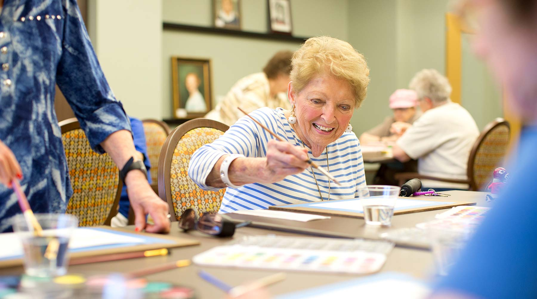 A women painting in the art room at Kingswood Senior Living Located in Kansas City, MO.