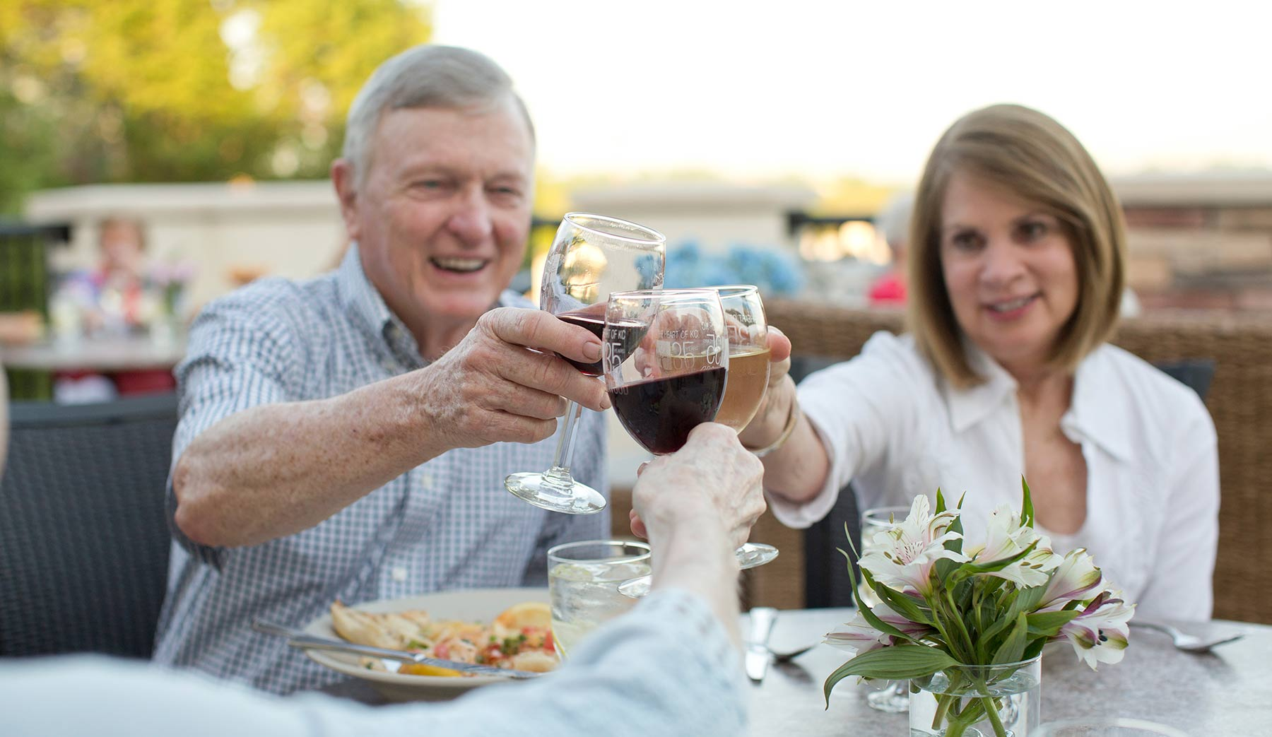 A couple enjoying wine on the porch at Kingswood Senior Living Located in Kansas City, MO.