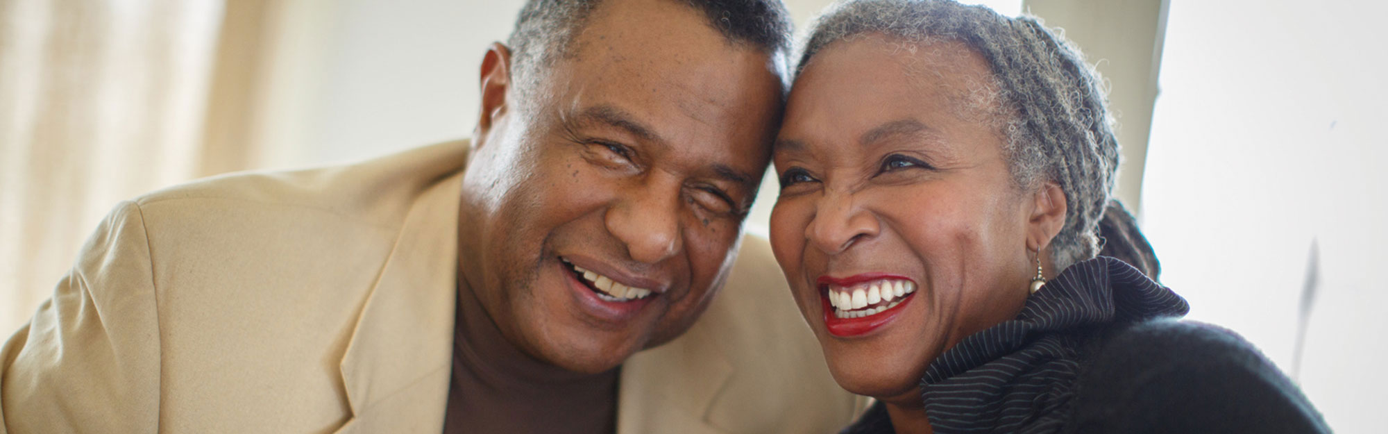 A couple in a apartment smiling at Kingswood Senior Living Located in Kansas City, MO.