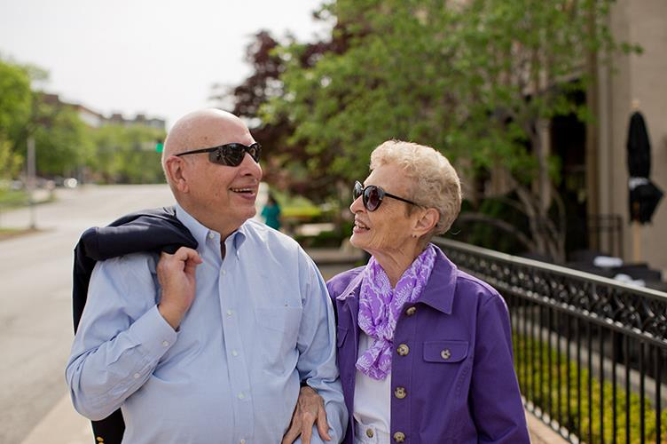A couple walking down the sidewalk at Kingswood Senior Living Located in Kansas City, MO.