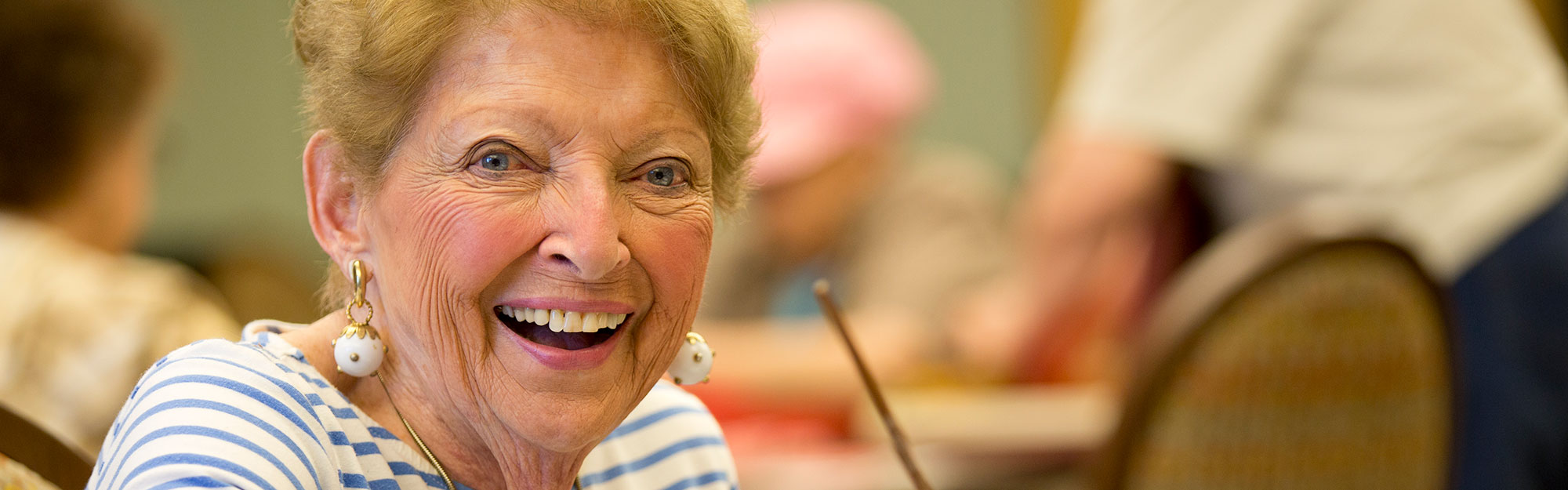 A women looking at the camera and smiling at Kingswood Senior Living Located in Kansas City, MO.