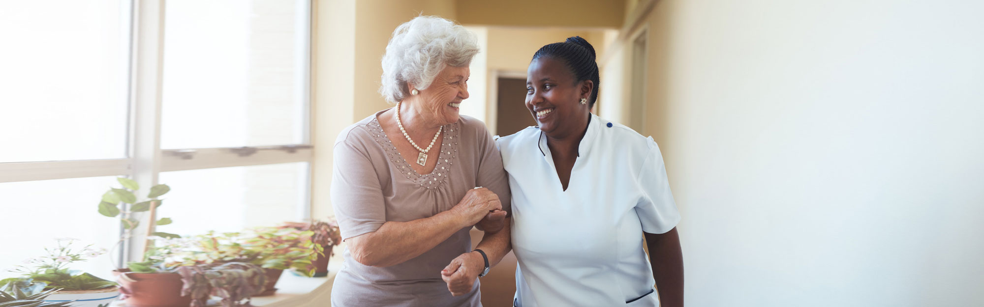 senior woman arm-in-arm with caregiver smiling while walking down a hallway