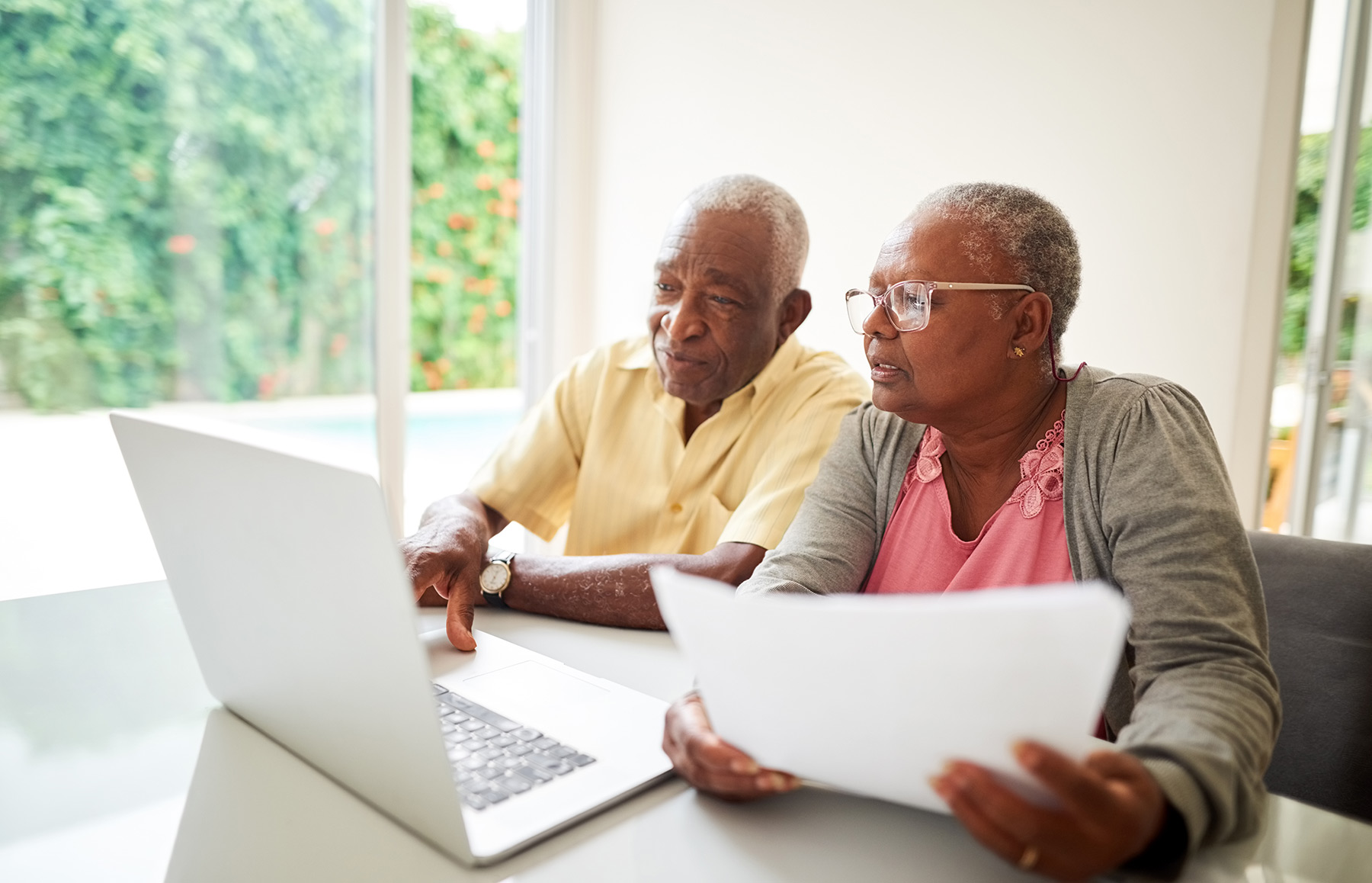 Couple looking at finances and a computer to prepare to compare a Entrance Fee vs. Rental Community